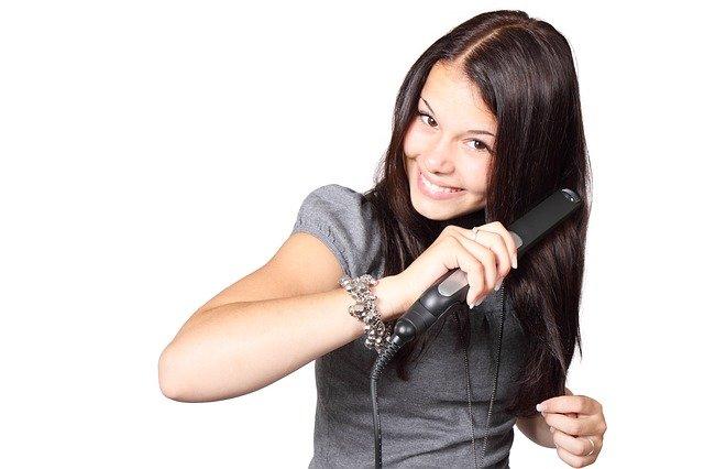 dívka žehlící si vlas
