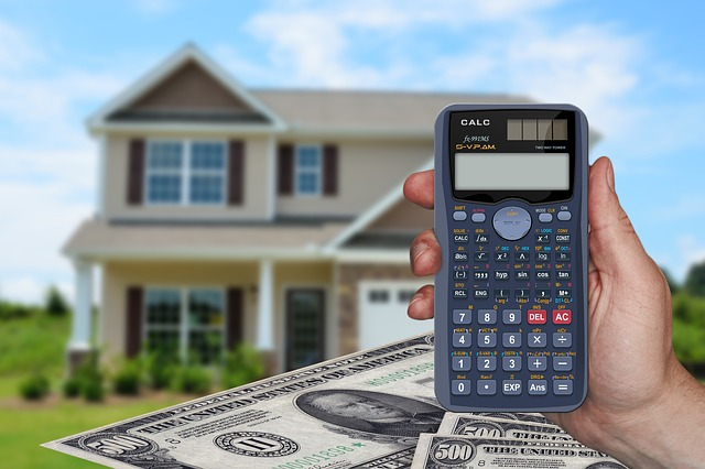 peníze, kalkulačka a v pozadí dům