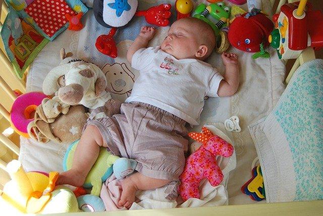 spící miminko obklopené hračkami