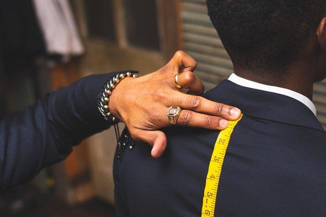člověk měřící muže v obleku